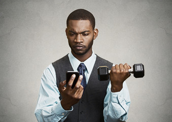 Businessman reading text message on mobile lifting weight simult