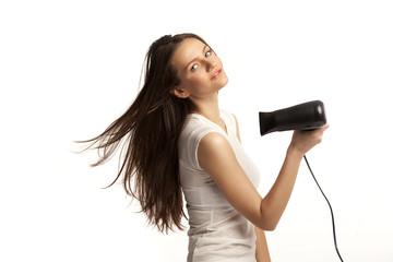 Beautiful smiling young woman drying her hair