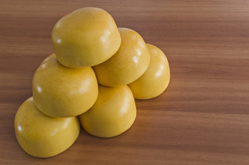 Yellow shiny cow cheese against a wooden background