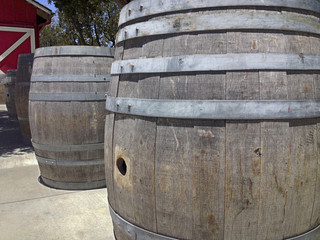 Big wooden barrels lined up next to red barn door