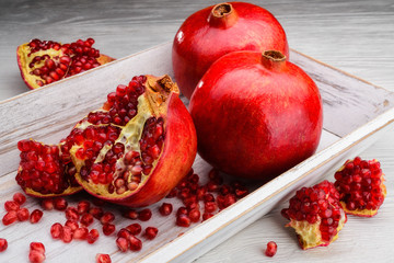 pomegranate fruits on white wooden background