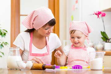 kid girl with her mother cooking in the kitchen