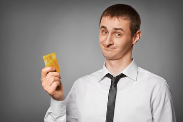 smiling young man holding a credit card
