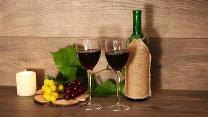 red wine in two glasses sways on the wooden background