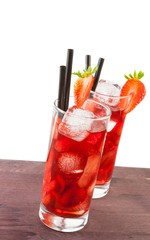 two glasses of strawberry cocktail with ice on white background