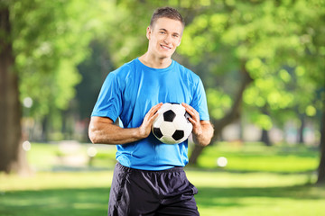 Young man holding a football in the park