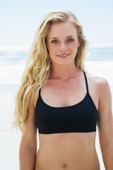 Fit blonde smiling at camera on the beach