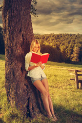 Young woman reading a book in the nature