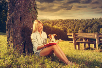 Young woman reading a book in the nature with her dog