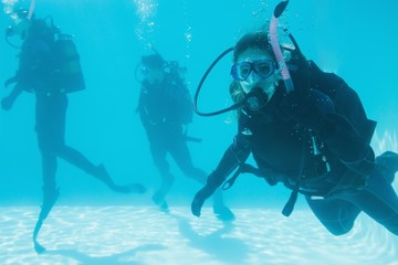 Friends on scuba training submerged in swimming pool one looking