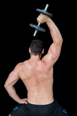 Strong crossfitter lifting up heavy black dumbbell above head