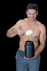 Happy muscular man scooping up protein powder