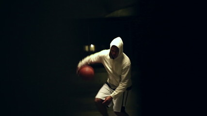 Basketball player dribbling the ball at night