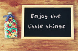 bottle filled with candies and blackboard with the phrase enjoy