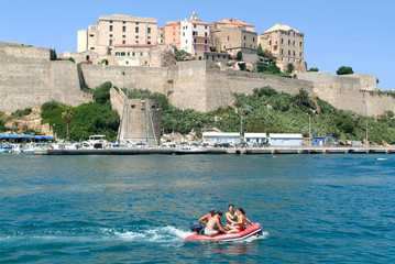 People on a boat in front of Calvi at Corsica island