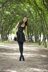 Lady in black dress in summer park
