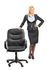 Businesswoman standing by an office chair