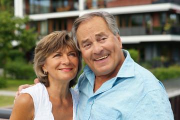 Älteres Paar vor ihrem Wohnhaus