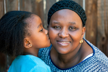 African girl kissing mother on cheek.