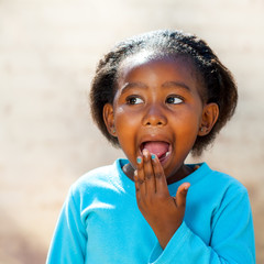 African girl with hand on open mouth.