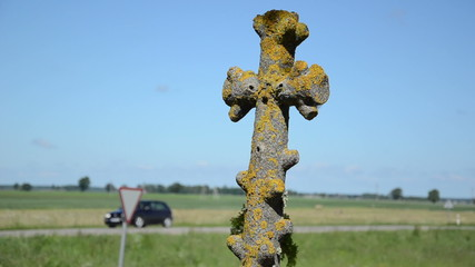 Retro mossy stone cross closeup and car drive on background