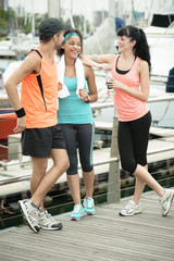 Three young friends chatting after morning exercise