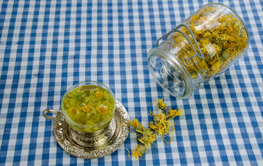healing marigold tea and jar dried flower on table