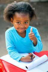 African student doing thumbs up at table.