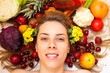 Smiling female face surrounded with lot of fruit and vegetables