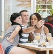 Young attractive mixed race group taking selfie at coffee shop