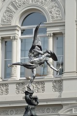 Eros statue with arch in background