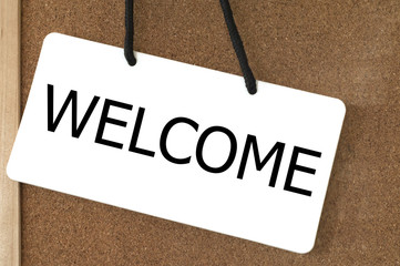 Welcome sign label on wooden board.