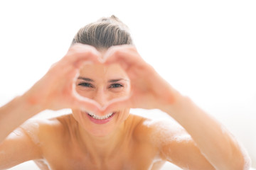 Young woman in bathtub looking through heart shaped hands