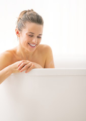 Portrait of happy young woman in bathtub