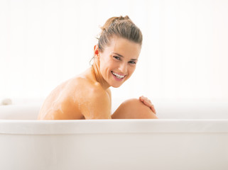 Young woman sitting in bathtub