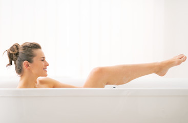 Young woman washing in bathtub