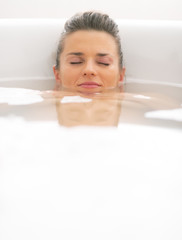 Relaxed young woman laying in bathtub