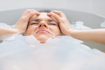 Stressed young woman laying in bathtub