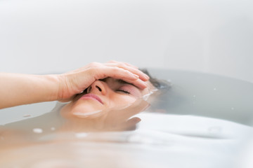 Frustrated young woman laying in bathtub