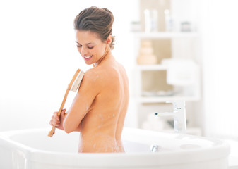 Young woman using body brush in bathtub
