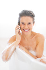 Happy young woman talking mobile phone in bathtub