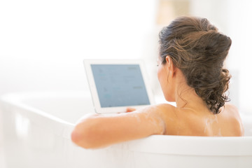 Young woman using tablet pc in bathtub. rear view