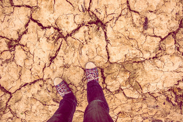 background feet in sneakers and jeans standing on dry soil