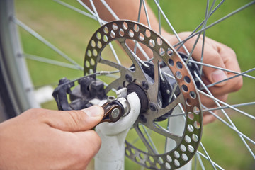 Man cyclist checks brake wheel of bicycle