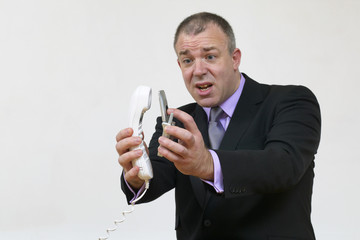 Businessman having animated conversation on telephone,