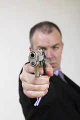 man in suit with gun
