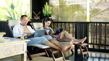 Couple with laptop relaxing on terrace in tropical place