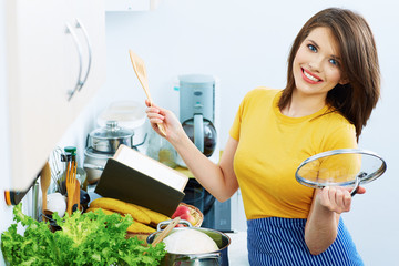 Woman cooking in kitchen with menu book.