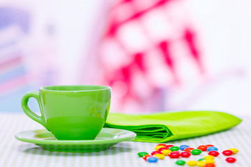 Tea cup and candy.dragees on the table