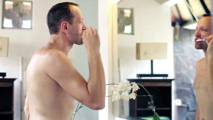 Young shirtless man brushing his teeth in bathroom